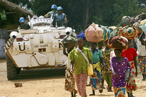 Villagers pass a UN patrol unit in DR Congo