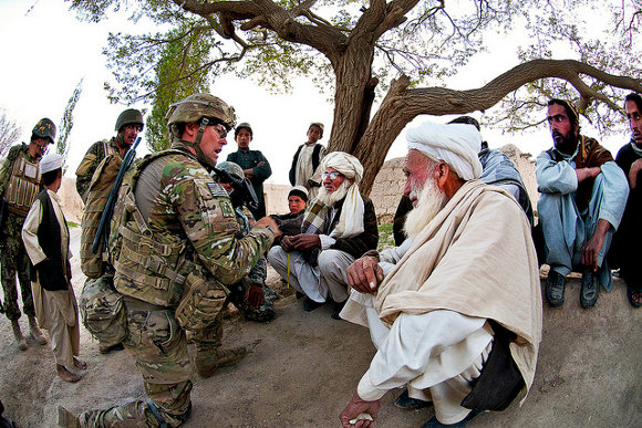 A US army soldier meets with village elders in Afghanistan