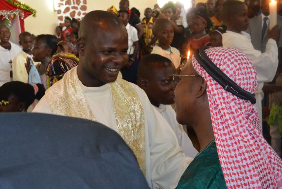 Catholic priest greeting Muslim leader after prayers