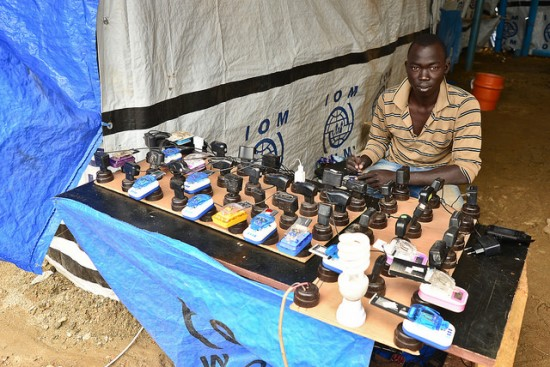 A young man charges phones at a UN IDP camp in South Sudan. Image credit: https://flic.kr/p/ndpFQb by Tom McShane