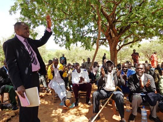 A peace and reconciliation meeting between Pokot and Sabiny communities, facilitated by Rev Nahashion (standing). These meetings take place as part of POKATUSU's peace caravans.